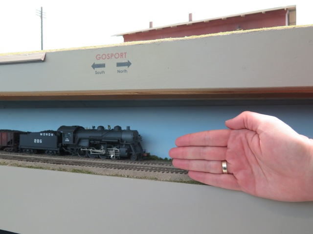 "One of the branch staging yards is under the layout.  I did not notice it until I was about to leave.  It is effective and I like the blue backdrop.    My hand is there for ""scale"" so you can see how small the space is."