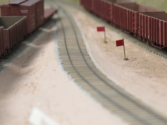 The mainline and some spurs are on grade. When switching, a red flag can be inserted into a tube between the ties to hold that cars in place by the coupler.