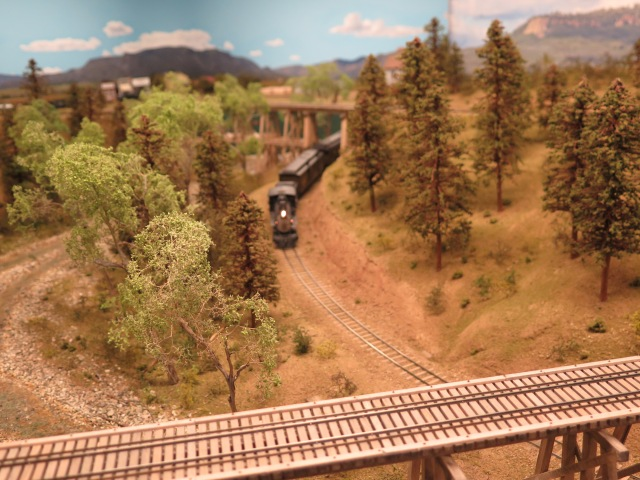 A train passes under the trestle